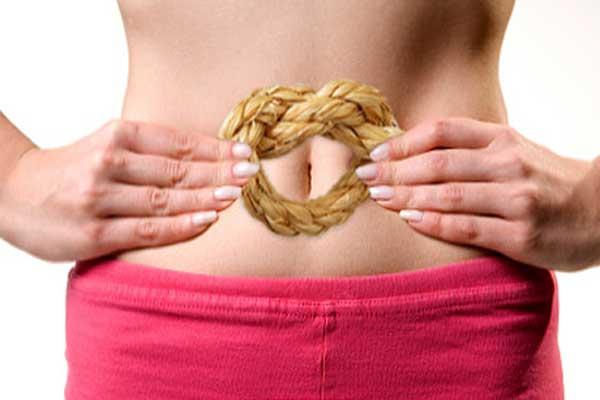 Пищевые волокна от запора, девушка в розовой юбке держит у живота пшеничный рогалик