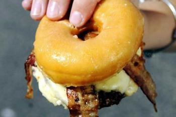 Жирный чизбургер с беконом, жир стекает по руке