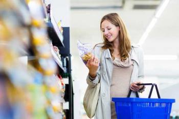 Женщина в магазине держит в руках голубую корзинку и выбирает хорошую еду