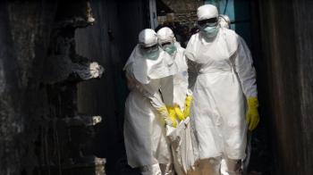 Члены Красного Креста в защитной одежде перемещают тело погибшего от лихорадки Эбола  Фото ZOOM DOSSO / AFP