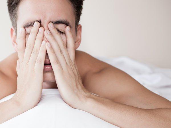 Ночная эпилепсия - мужчина держится за голову, руками закрывает глаза