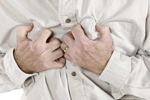 Чем может быть вызвана боль в груди - мужчина держится за свою грудь, пальцы рук скрючены от боли