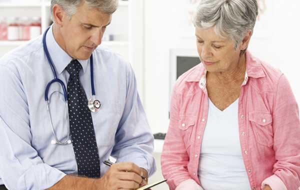 Врач объясняет женщине как восстанавливаться после сердечного приступа