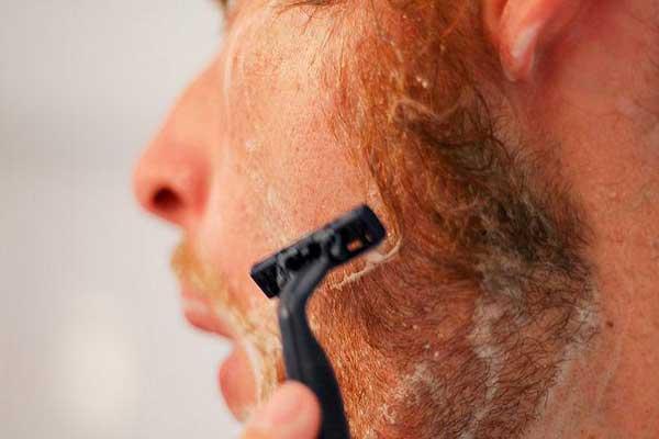 Мужчина бреет рыжие волосы одноразовым станком сверху вниз - чтобы не было раздражения после бритья