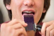 мужчина пробует как работает новый прибор от глухоты