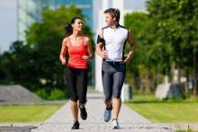 Женщина и мужчина бегут трусцой по зеленой аллее