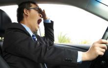 Сонливость и усталость за рулем, мужчина в костюме зевает за рулем