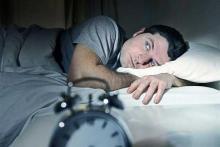 Короткий сон приводит к диабету, мужчина лежит в темноте на кровати рядом будильник