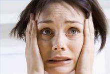 Сильная головная боль: женщина закатывает глаза и трет виски