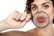 Девушка брюнетка с карими глазами, девушка держит лупу, большие губы, зуд на губах