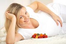 Родить ребенка после 35 лет - беременная женщина улыбается и кушает фрукты