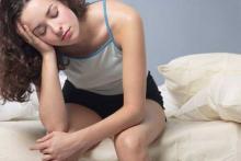Первые признаки беременности до задержки - девушка сиди на кровати ее мутит