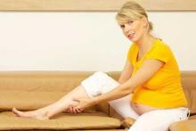 Женщина в желтой кофте демонстрирует варикозное расширение вен во время беременности